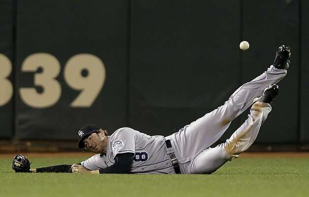 Colorado Rockies left fielder Charlie Blackmon (8) cannot make a diving catch on a fly ball by San Francisco Giants' Angel Pagan during the eighth inning of a baseball game on, Tuesday, Sept. 18, 2012 in San Francisco.  Pagan drove in a run with a triple on the play. (AP Photo/Marcio Jose Sanchez) Photo: Marcio Jose Sanchez, Associated Press