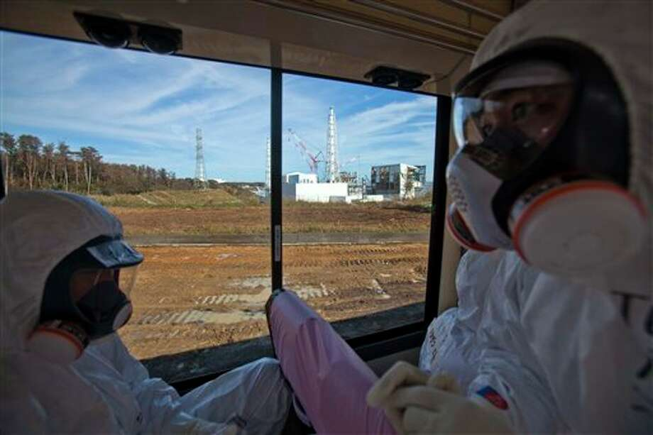 FILE - In this Nov. 12, 2011 file photo, an official from the Tokyo Electric Power Co., right, and an unidentified man, both wearing protective suits and masks ride on a media bus as they pass by the crippled Fukushima Dai-ichi nuclear power station, seen through the window, in Okuma, Japan. Japan was woefully unprepared for last year's nuclear disaster, the country's former prime minister said Friday, March 2, 2012, and suggested that the crippled Fukushima plant should not have been built so close to the ocean on a tsunami-prone coast. Photo: David Guttenfelder, AP / AP Pool