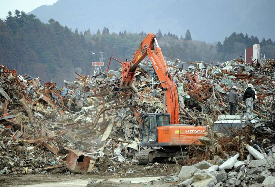 Heavy machinery removes the remnents of tsunami devastation in Rikuzentakata city, Iwate prefectura on March 8, 2012. Japan is readying to mark the first anniversary of the huge earthquake and tsunami that devastated the northeast coast on March 11, sparking a nuclear crisis at Fukushima. More than 19,000 people died in the disaster and hundreds of thousands were made homeless.      AFP PHOTO / TOSHIFUMI KITAMURA Photo: TOSHIFUMI KITAMURA, AFP/Getty Images / AFP