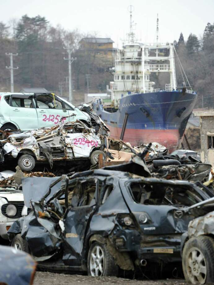 The 330 ton fishing vessel Kyotoku Maru No. 18 that was carried from Kesennuma port by the March 11 tsunami, lies behind destroyed cars at Kesennuma on March 8, 2012.   Japan is readying to mark the first anniversary of the huge earthquake and tsunami that devastated the northeast coast on March 11, sparking a nuclear crisis at Fukushima.  More than 19,000 people died in the disaster and hundreds of thousands were made homeless.    AFP PHOTO / TOSHIFUMI KITAMURA Photo: TOSHIFUMI KITAMURA, AFP/Getty Images / AFP