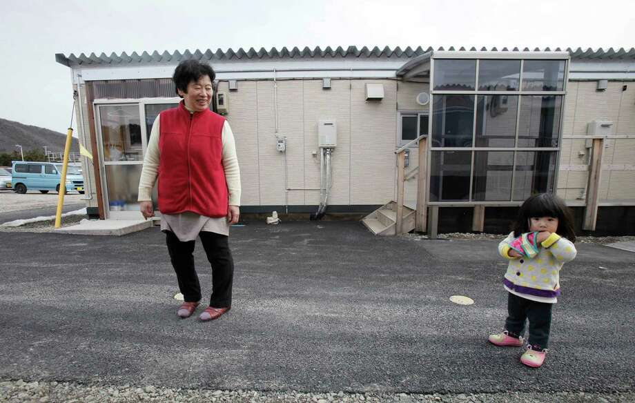 CORRECTS TOMIKO'S NAME - One-year-old girl Rin Yokota, right, is accompanied by her grandmother Tomiko Igari, 63, as they walk in the compound of their temporary housing in Otama village, Fukushima Prefecture, northern Japan, Thursday, March 8, 2012. Nearly one year after the March 11 earthquake and tsunami crippled the Fukushima Dai-ichi nuclear power station, many of the 100,000 people who have been evacuated from the 20-kilometer (12-mile) no-go zone still live in the similar housing complex in Fukushima. (AP Photo/Koji Sasahara) Photo: Koji Sasahara, Associated Press / AP