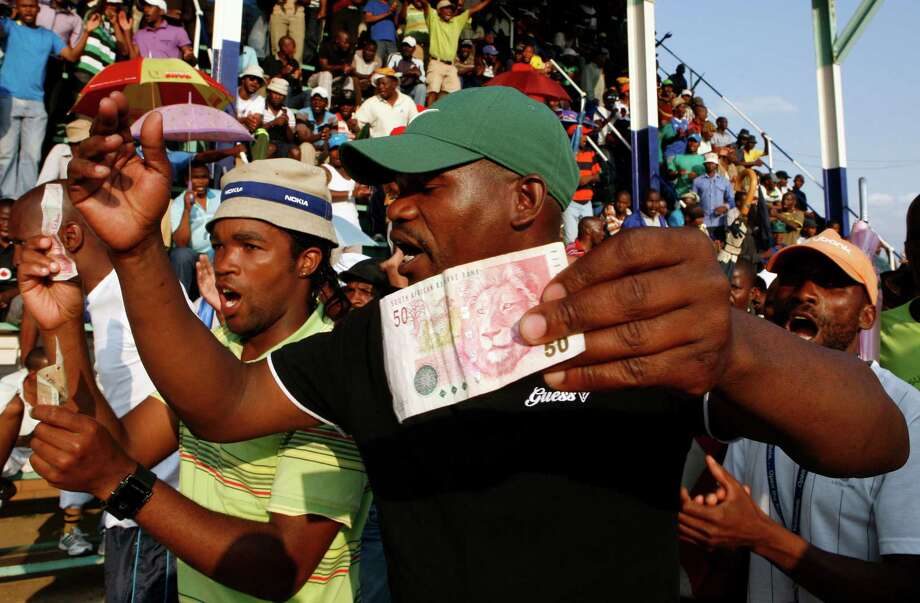 Miners sing and dance whilst holding South African bank notes in Lonmin Platinum Mine near Rustenburg, South Africa, Tuesday, Sept. 18, 2012. Striking miners have accepted a company offer of a 22% overall pay increase to end more than five weeks of crippling and bloody industrial action. (AP Photo/Themba Hadebe) Photo: Themba Hadebe, Associated Press / AP