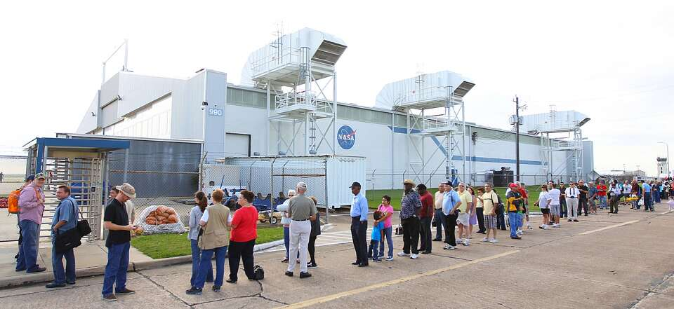 A line of space enthusiasts wait to enter the Ellington Field landing strip to see the space shut