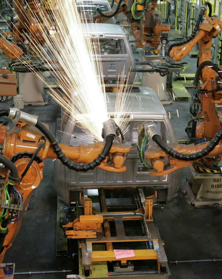 "Robots weld a truck cab at a Chrysler plant in Michigan. As new generations of super ""smart"" robots perform more complex tasks, what will happen to the workers they replace? Photo: Associated Press File Photo / AP"