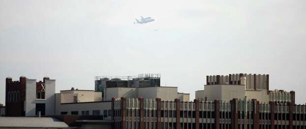 The space shuttle Endeavour flies over the University of Houston Downtown building, downtown Houston, Wednesday, Sept. 19, 2012, in Houston. Photo: Karen Warren, Houston Chronicle / © 2012  Houston Chronicle
