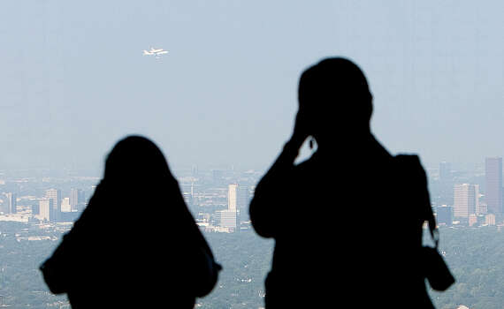 Observers watch from the Chase Tower as the the space shuttle Endeavour makes a pass over Houston Wednesday, Sept. 19, 2012, in Houston. Photo: Cody Duty, Houston Chronicle / © 2012 Houston Chronicle
