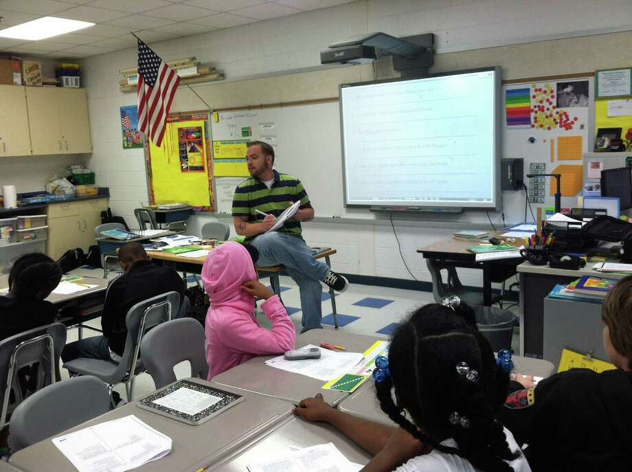 Jeff Beckley, a fifth-grade teacher at Kendall Elementary School, uses the INTERWRITE Mobi, a mobile interactive whiteboard system used in conjunction with the Classroom Performance System (CPS) clickers, with his students recently. Photo: Contributed Photo