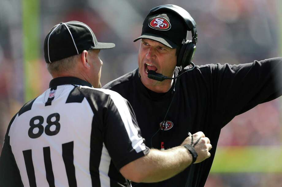 FILE - This Aug. 26, 2012 file photo shows San Francisco 49ers head coach Jim Harbaugh, right, arguing with a replacement official during the second quarter of an NFL preseason football game against the Denver Broncos,  in Denver. The NFL will open the regular season with replacement officials. League executive Ray Anderson has told the 32 teams that with negotiations remaining at a standstill between the NFL and the officials' union. The replacements will be on the field beginning next Wednesday night, Sept. 5, 2012 when the Cowboys visit the Giants to open the season. (AP Photo/Joe Mahoney, File) Photo: Joe Mahoney, Associated Press / FR170458 AP