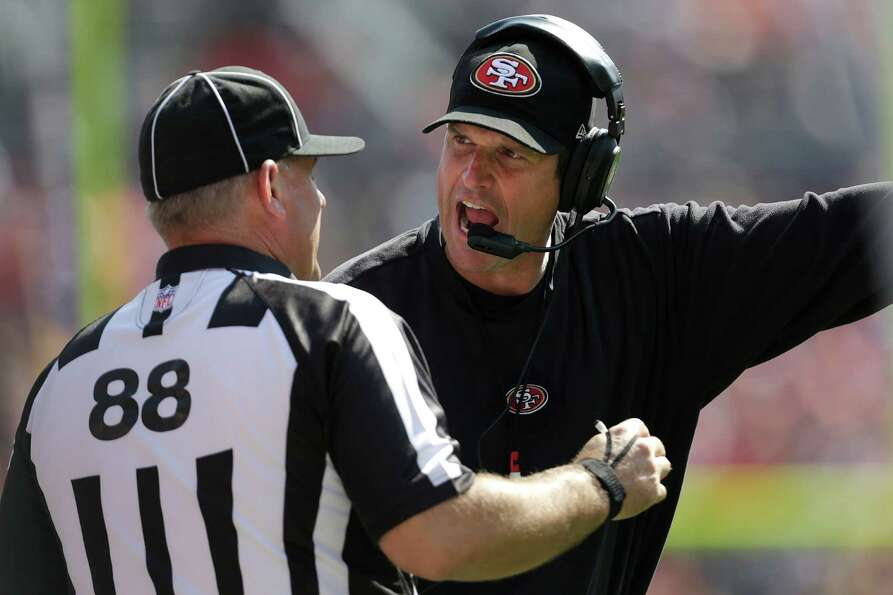 FILE - This Aug. 26, 2012 file photo shows San Francisco 49ers head coach Jim Harbaugh, right, argui