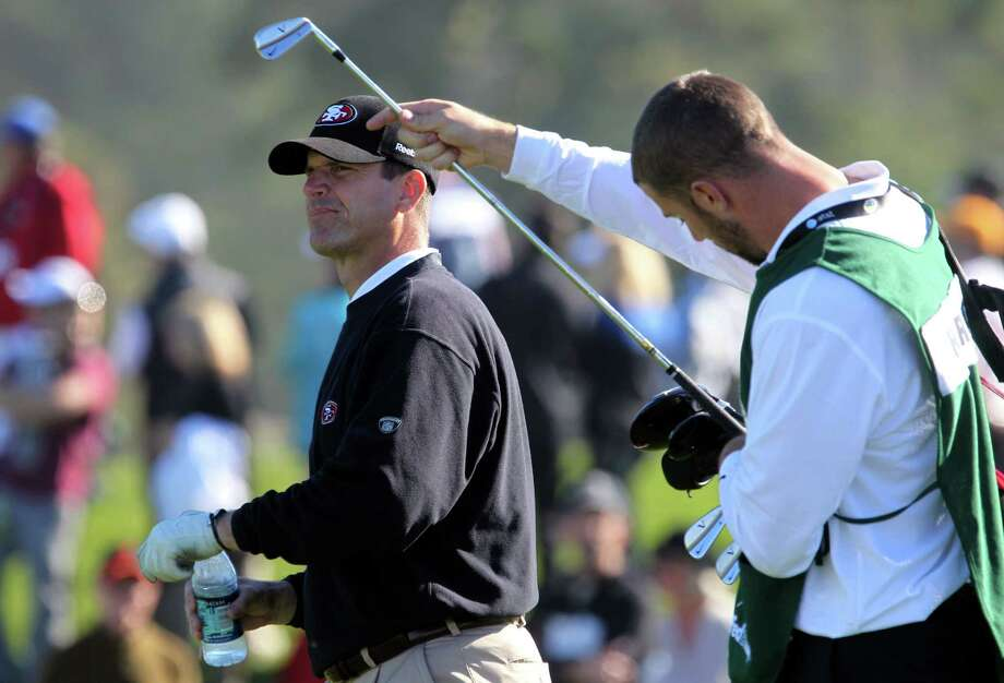 San Francisco 49ers coach Jim Harbaugh and his caddie 49ers quarterback Alex Smith walked up the fourth fairway Thursday, February 9, 2012 during opening rounds of the annual AT&T Pebble Beach National Pro-Am golf tournament in Pebble Beach, Calif. Photo: Lance Iversen, The Chronicle / ONLINE_YES
