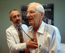 In this June 19, 2012 photo, Dr. Bruce Stowell examines patient Robert Busch at his office in Grants Pass, Ore. Stowell is among many doctors in rural areas who have capped the numbers of Medicare patients they take due to low reimbursement levels. A nationwide shortage of primary care physicians willing to set up practice in rural areas is making the problem worse. (AP Photo/Jeff Barnard)