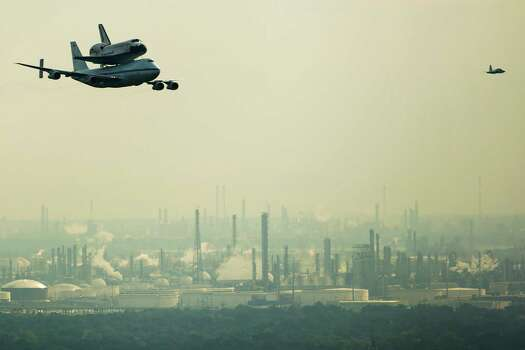The space shuttle Endeavour, carried atop NASA's 747 Shuttle Carrier Aircraft, passes over petrochemical facilities on the Houston Ship Channel during a flyover on Wednesday, Sept. 19, 2012, in Houston. Endeavour stopped in Houston on its way from the Kennedy Space Center to the California Science Center in Los Angeles, where it will be placed on permanent display. Photo: Smiley N. Pool, Houston Chronicle / © 2012  Houston Chronicle