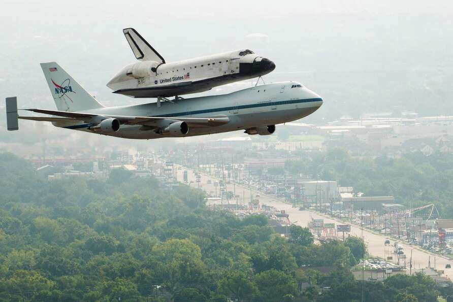 The space shuttle Endeavour, carried atop NASA's 747 Shuttle Carrier Aircraft, passes over neighborh