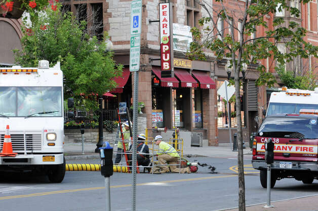 A crew works on a manhole on North Pearl Street after reports of an explosion causing manhole covers to lift off the ground Wednesday. (Lori Van Buren / Times Union)