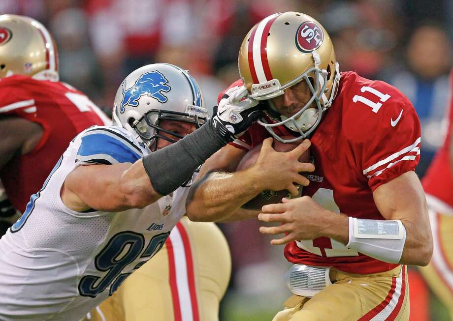 San Francisco 49ers quarterback Alex Smith, right, and Detroit Lions defensive end Kyle Vanden Bosch, left, are seen in action during the second quarter of an NFL football game in San Francisco, Sunday, Sept. 16, 2012. Photo: Tony Avelar, Associated Press / AP