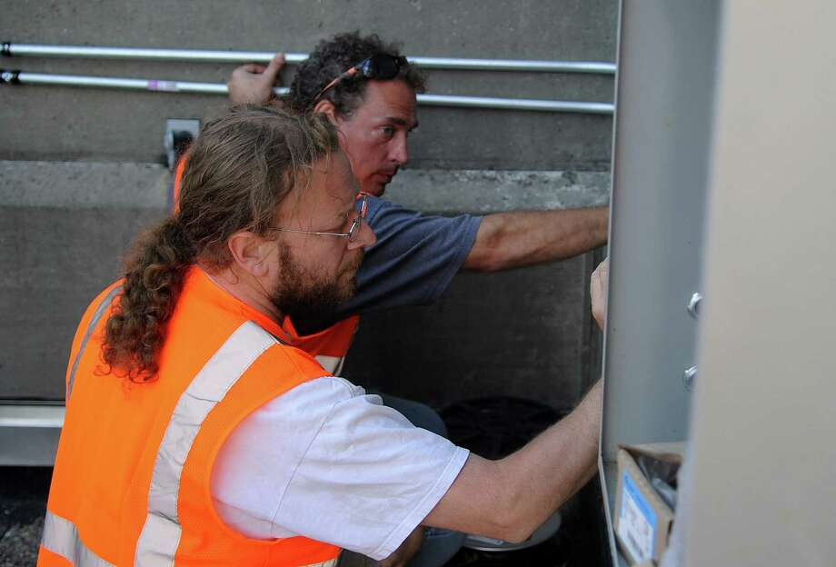 Jamie Burnett, back, and Rich Burkam, front, work to install LED lights on the outside of the Stamford Train Station on Wednesday, September 19, 2012. The lights are part of the city's Festival of Lights this weekend. Photo: Lindsay Niegelberg / Stamford Advocate