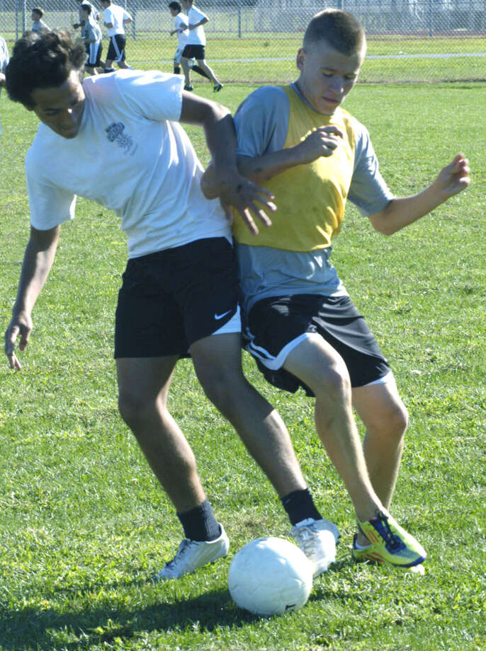 Kevin Ferrera, left, and Cole Case demonstrate no holds barred hustle during pre-season for New Milford High School boys' soccer, September 2012 Photo: Norm Cummings