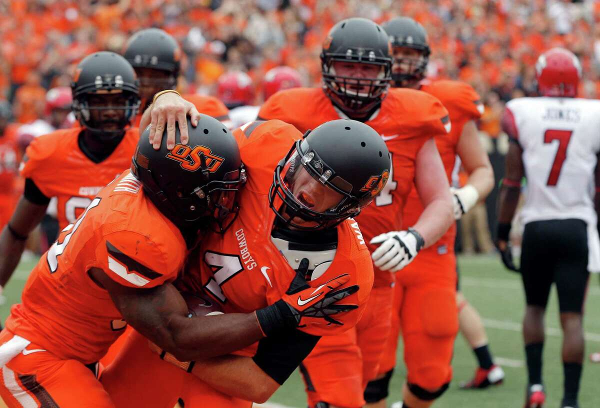 Quarterback J.W. Walsh (center) and Oklahoma State have scored 84 and 65 points in their two victories this season.
