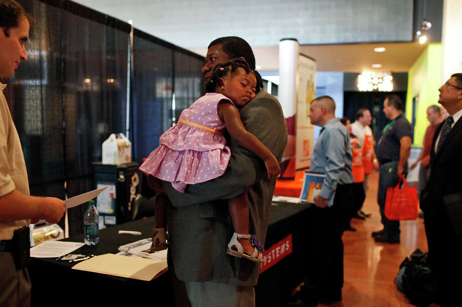 "Wounded Warrior Sgt. First Class (Ret.) Michael Jenkins holds his sleeping daughter, Camilla Jenkins, 19 months, as he talks to Joe Moore, a task manager with BAE Systems, left, during the RecruitMilitary Veteran job fair at the AT&T Center in San Antonio on Thursday, Sept. 13, 2012. Jenkins suffered three strokes while serving his second deployment to Iraq, leaving him with a Traumatic Brain Injury. He had to retire after 23 years in the Army seven months ago. Now at home full time with his daughter, Jenkins says he is looking for a new career. ""That's all I know, that's my life,"" Jenkins says of his former Army career. Photo: Lisa Krantz, San Antonio Express-News / San Antonio Express-News"
