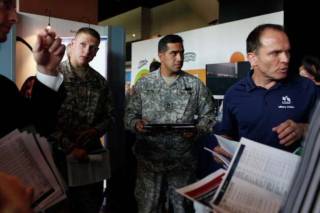 Wounded Warriors Sgt. Cody Winstead, left, and Sgt. First Class Raymond Soto, right, listen to Romey Pelletier, far right, with USAA Military Affairs, during the RecruitMilitary Veteran job fair at the AT&T Center in San Antonio on Thursday, Sept. 13, 2012. Winstead was injured in Afghanistan in 2012 and Soto was inured in Afghanistan in 2003. Photo: Lisa Krantz, San Antonio Express-News / San Antonio Express-News