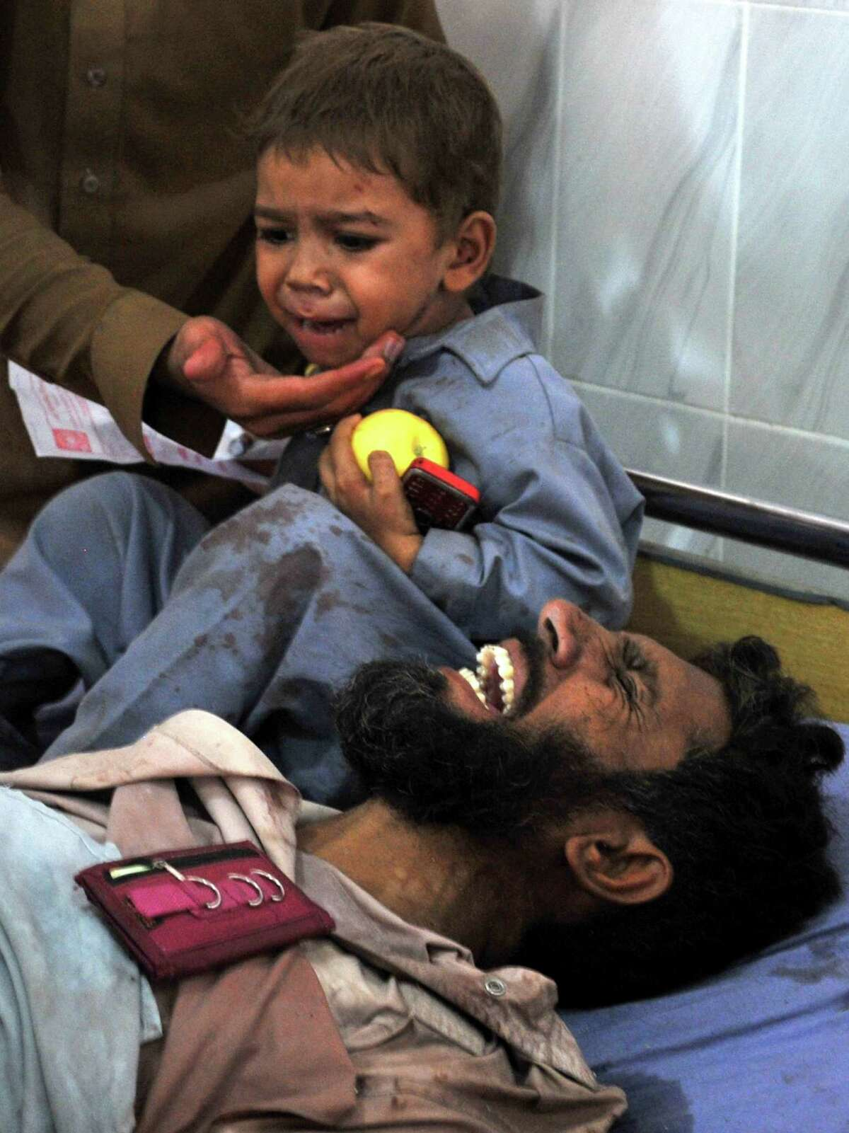 TOPSHOTS A Pakistani child cries to his injured father at a hospital following a bomb explosion in Peshawar on September 19, 2012. A bomb apparently targeting a Pakistan air force vehicle ripped through a van in the country's northwestern city of Peshawar on September 19, killing nine people, officials said. AFP PHOTO / HASHAM AHMEDHASHAM AHMED/AFP/GettyImages