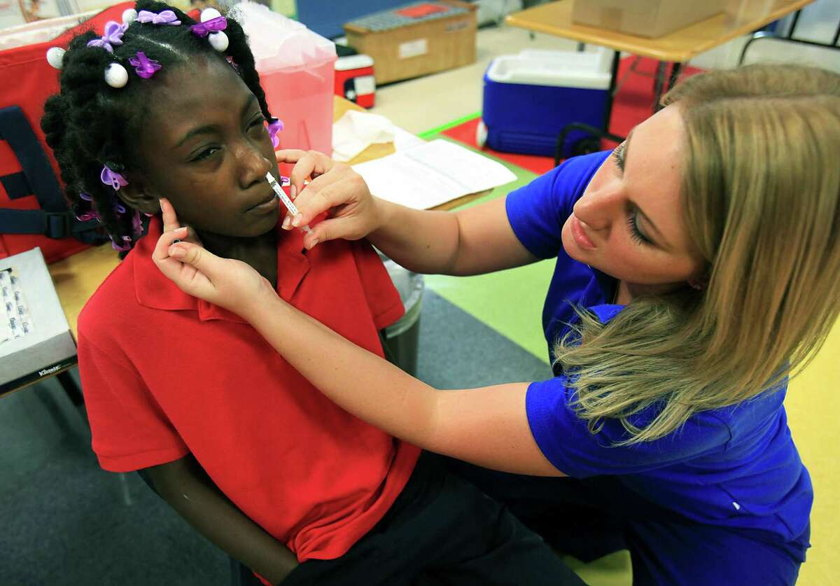 Shauna Shaw, right, of Little Spurs Urgent Care Center, administers the flu vaccine to Torrian Sumlin, a 5th grader at Larkspur Elementary School. Brandi Chastain, Olympian, and World Cup Soccer champion, visited Larkspur Elementary School to support the school's distribution of flu vaccines through the San Antonio Metropolitan Health District. Wednesday, Sept. 19, 2012.