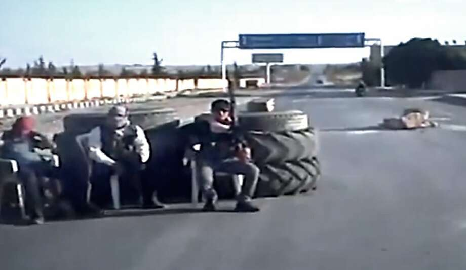 In this image taken from video obtained Wednesday, Sept. 19, 2012 from the Ugarit News, which has been authenticated based on its contents and other AP reporting, Free Syrian Army soldiers sit at a check point in Ain al-Arous town in Raqqa, Syria on Tuesday, Sept. 18, 2012. (AP Photo/Ugarit News via AP video) Photo: Uncredited, Associated Press