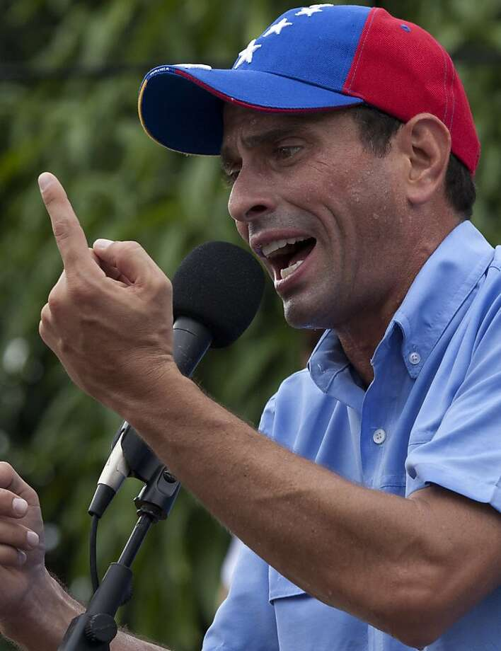 Henrique Capriles leads Hugo Chavez, 48.1 percent to 46.2. Photo: Ariana Cubillos, Associated Press