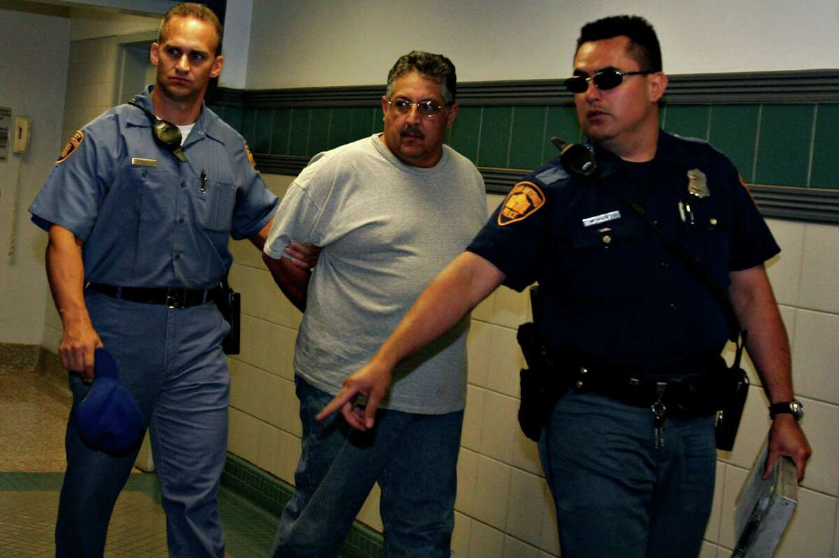Adrian Mendoza is escorted from the San Antonio Police Department, Thursday, April 27, 2006. He was taken into custody in connection with the murder of Paul Samudio.