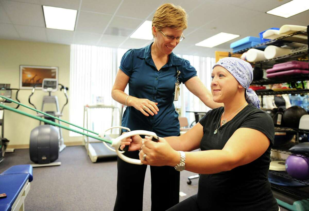 Heidi Taylor, of Trumbull, works with therapist Vikki Winks Tuesday, Sept. 18, 2012 at Ahlbin Rehabilitation Center in Stratford. Taylor is a breast cancer survivor and is undergoing medical treatment at Bridgeport Hospital following surgery. The therapy helps Taylor manage the effects of cancer treatment.