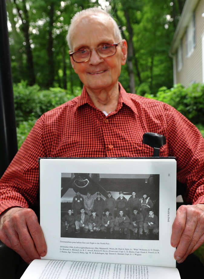 Ernest Stewart, holds up a photo showing him and the rest of the B-29 crew that flew over the North Pole in 1946, as he poses at his home in Shelton, Conn. on Friday September 7, 2012. Photo: Christian Abraham / Connecticut Post