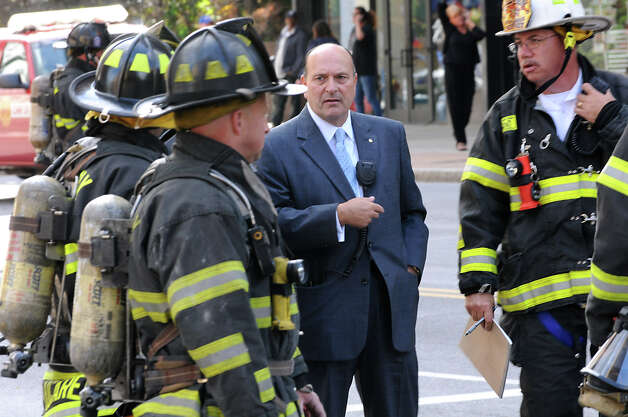 Albany Fire Chief Robert Forezzi talks with firemen on North Pearl St. after an underground gas explosion caused manhole covers to go flying Wednesday, Sept. 19, 2012 in Albany, N.Y. (Lori Van Buren / Times Union) Photo: Lori Van Buren