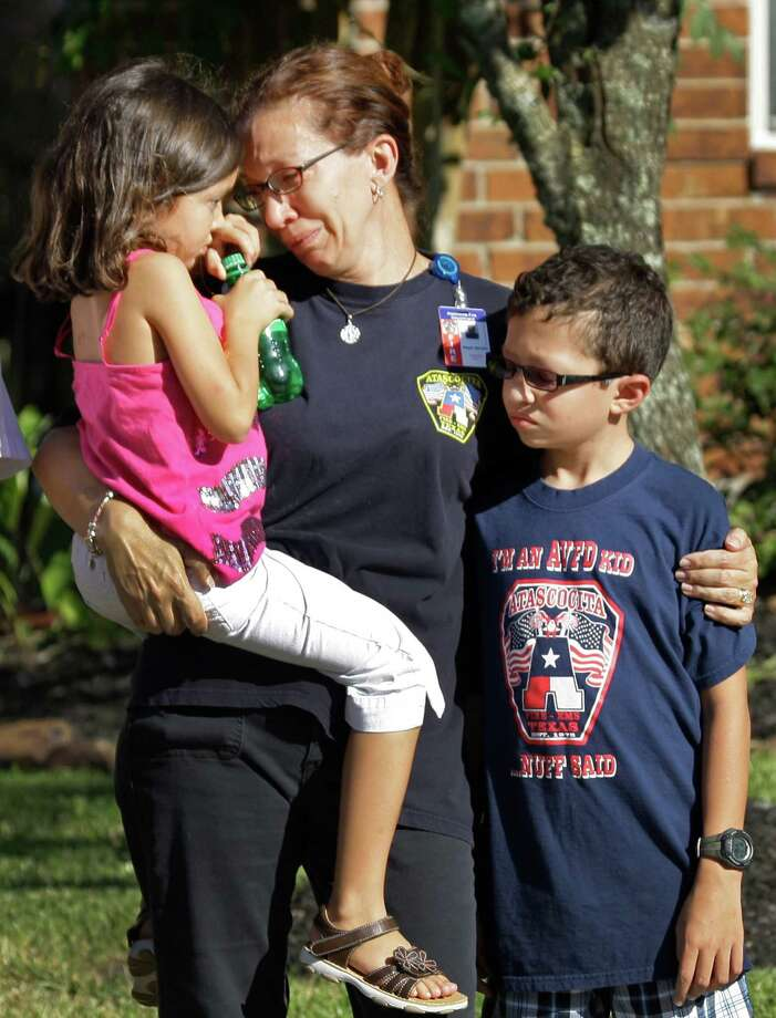 Penny Smith hugs her children, Natalie, 7, and Nicholas, 11, after      an Atascocita Volunteer Fire Department ambulance carrying the body of her      husband and their father, Capt. Neal Smith, passed their home during a procession on Wednesday. Photo: Melissa Phillip, Houston Chronicle / © 2012 Houston Chronicle