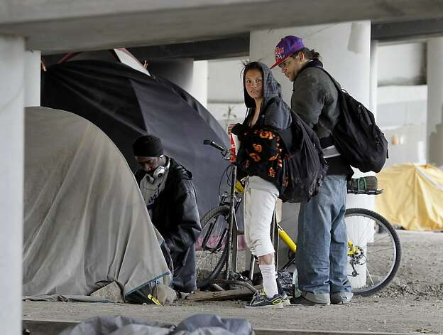 Homeless people paused beneath the freeway overpass in the encampment near where the fire started. A persistent homeless encampment at the highway 280 onramp at King Street in San Francisco, Calif. was the scene of a fire Wednesday September 19, 2012.  This is the same location where state and local authorities cleared out a large homeless camp several weeks ago. Photo: Brant Ward, The Chronicle