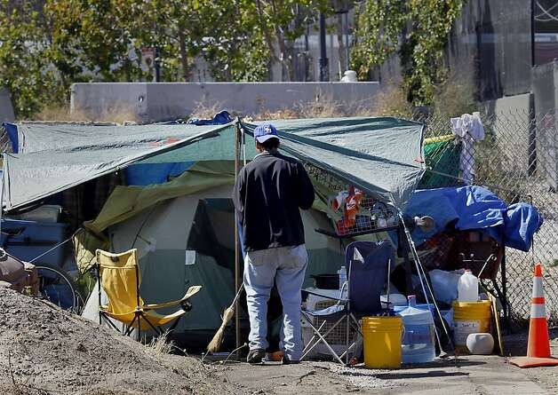 A man sweeps the entrance to his tent at a homeless encampment near the Interstate 280 on-ramp at Fifth and King streets. Photo: Brant Ward, The Chronicle