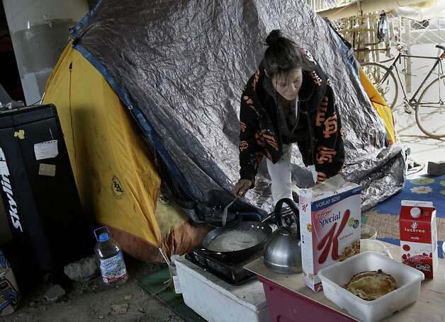 A homeless woman who did not want to give her name made breakfast beneath the highway, a stones throw from where the fire broke out. A persistent homeless encampment at the highway 280 onramp at King Street in San Francisco, Calif. was the scene of a fire Wednesday September 19, 2012.  This is the same location where state and local authorities cleared out a large homeless camp several weeks ago. Photo: Brant Ward, The Chronicle