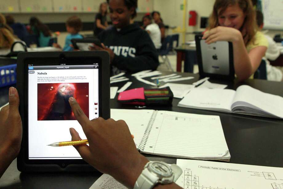 Cameron Webb, 13, looks up information about nebulas on a tablet during an eighth-grade science class Wednesday at Baines Middle School in Missouri City, part of the Fort Bend Independent School District. Photo: Johnny Hanson / © 2012  Houston Chronicle