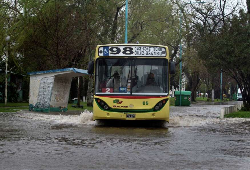 A bus crosses a street flooded due to the overflowing of the River Plate after a storm on September