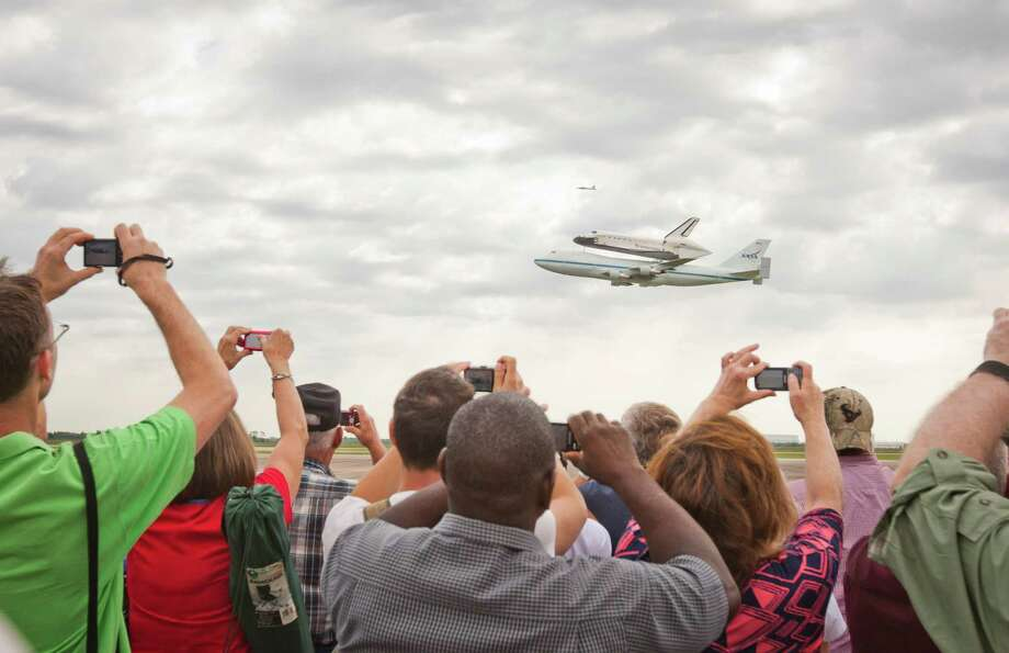 Aboard its 747 carrier, the space shuttle Endeavour does one of two low passes for the crowd Wednesday before its stopover at Ellington Field en route to California. Photo: Nick De La Torre / © 2012 Houston Chronicle