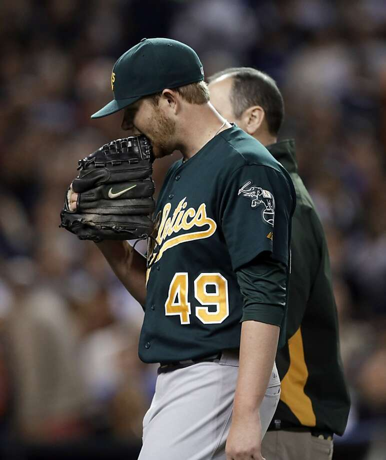 Oakland Athletics starting pitcher Brett Anderson (49) bites his glove while walking off the field with a trainer during the third inning of a baseball game against the Detroit Tigers in Detroit, Wednesday, Sept. 19, 2012. (AP Photo/Paul Sancya) Photo: Paul Sancya, Associated Press