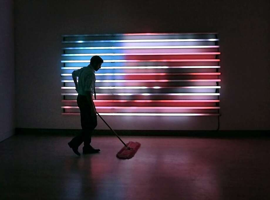 Collin McCanna, a gallery assistant with the Madison Museum of Contemporary Art in Madison, Wis., sweeps the floor in front of an LED light panel by American artist Leo Villareal at the museum Wednesday, Sept. 19, 2012. The recently-opened exhibit of the artist's large-scale light sculptures features computer-driven, non-repeating light patterns emitted from wall and ceiling-mounted installations. (AP Photo/ Wisconsin State Journal, John Hart) Photo: John Hart, Associated Press