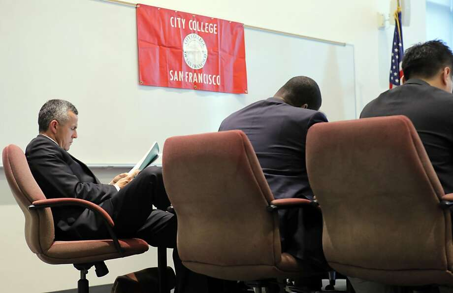 CCSF board member, Rodrigo Santos, left, reads the findings of the state's Fiscal Crisis & MAnagement Assistance Team, as members of the team speak to the board at a meeting at CCSF. The team put together to look into the financial crisis at City College of San Francisco delivered its findings to the CCSF Board of Trustees at City College in San Francisco, Calif., on Tuesday, September 18, 2012. Photo: Carlos Avila Gonzalez - San Fran, The Chronicle