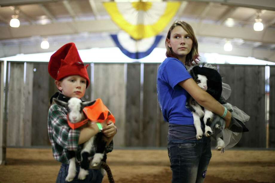 Ezekiel Meier, 6, and his sister Madison Meier, 13, of Graham hold their Nigerian dwarf goats as they participate in an animal costume contest at the Puyallup Fair, soon to be known as the Washington State Fair. Photo: JOSHUA TRUJILLO / SEATTLEPI.COM