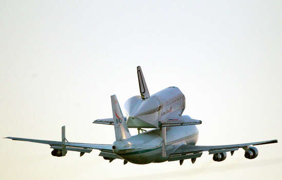The space shuttle Endeavour carried atop NASA's 747 Shuttle Aircraft flies through the air after leaving Ellington Field Thursday, Sept. 20, 2012, in Houston. Photo: Cody Duty, Houston Chronicle / © 2012 Houston Chronicle