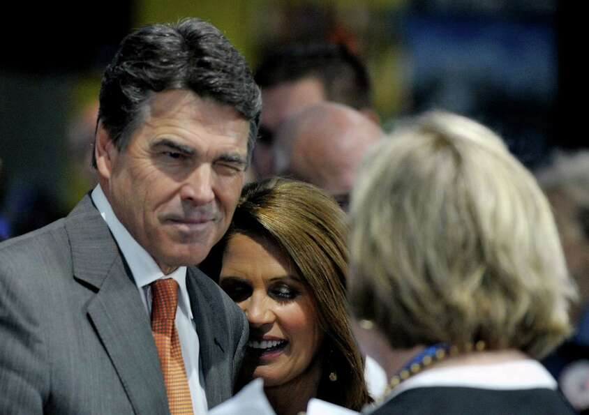 Former Republican party presidential candidate Governor Rick Perry jokes with an activist during a p