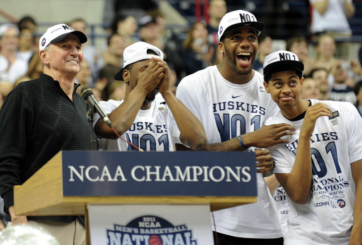 UCONN's Kemba Walker is overcome with emotion as his number is unveiled on the wall during a rally held for the men's basketball team at Gampel Pavilion in Storrs, Conn. on Friday April 5, 2011. With Walker on stage is Head Coach Jim Calhoun, left, and teammates Alex Oriakhi and Jeremy Lamb, at right.