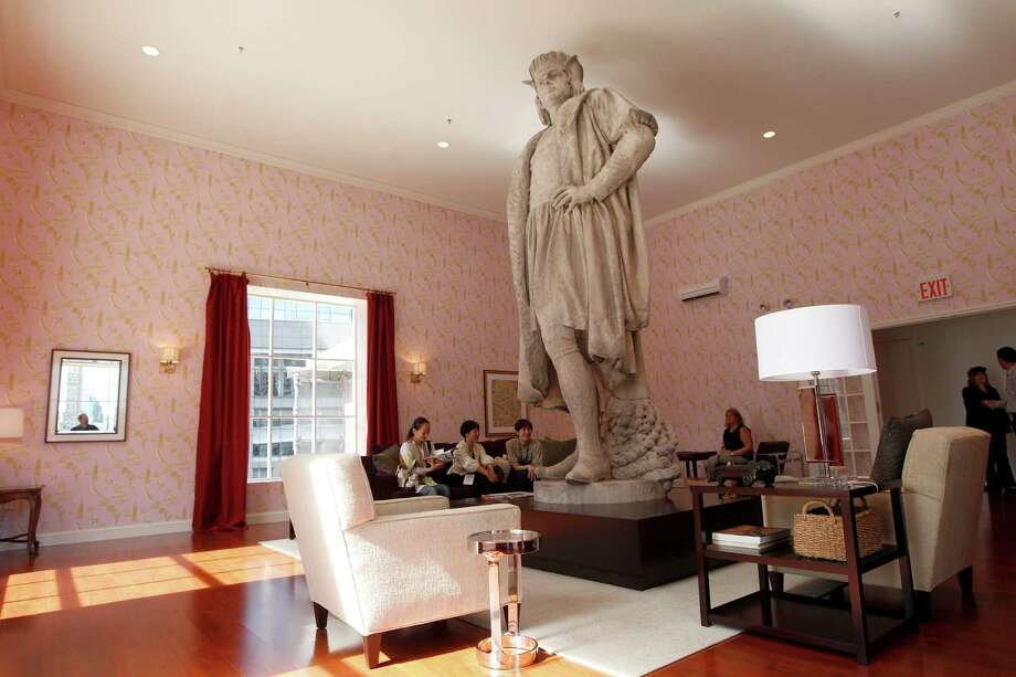 "Visitors take in the view during a media preview of ""Discovering Columbus,"" by Japanese artist Tatzu Nishi, Wednesday, Sept. 19, 2012 in New York's Columbus Circle.  The 810-square-foot living room built over the Columbus Monunment offers spectacular views of mid-Manhattan. The monument's 13-foot statue of Christopher Columbus stands amid the couches, lamps and coffee table. Photo: Mary Altaffer, AP / AP"