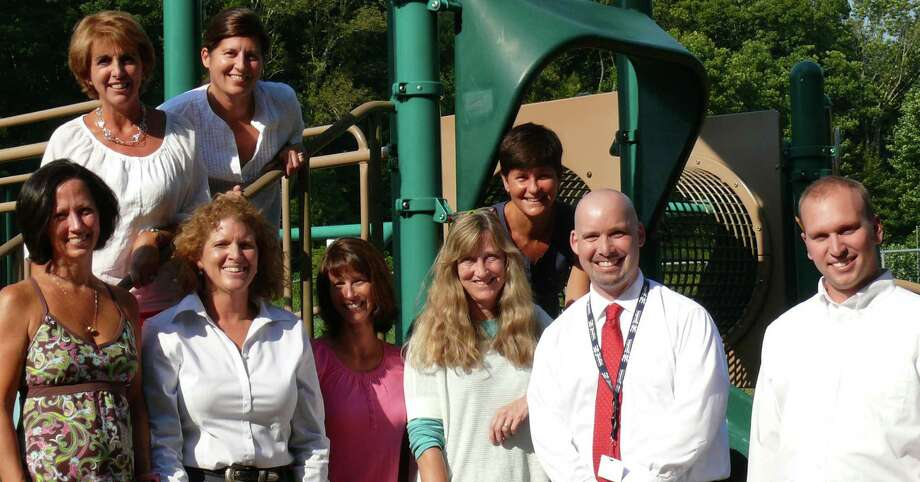 Gathered on the playground at Timothy Dwight School to discuss the school's recent designation as a National Blue Ribbon School by the federal Education Department are front row, from left, parent Kim Palmer, former Principal Brenda Anziano, parent Liz Neugebauer, librarian Kristen Robinson, Principal Scott Bannon and teacher Ryan Carroll; second row, teacher Joan Robb, Michele Whelan, a past PTA president, and PTA President Sue Voltz. Photo: Genevieve Reilly / Fairfield Citizen