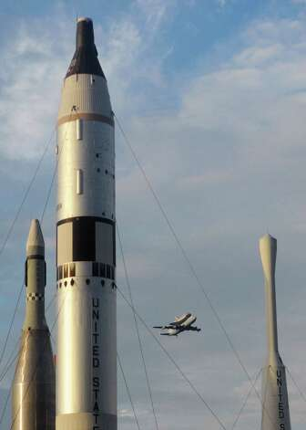 Flying over the rocket garden, space shuttle Endeavour passes over the Kennedy Space Center Visitor Complex on it's flight to a runway near NASA's Johnson Space Center in Houston Wednesday, Sept. 19, 2012 a one-day stop on its trek west to retirement in a California museum. Photo: Tim Shortt, AP / Florida Today