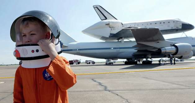 Joey Morrison adjusts his space helmet after watching the shuttle aircraft carrier with space shuttle Endeavour atop, land Wednesday, Sept. 19, 2012, at Ellington Field in Houston. Endeavour is making a final trek across the country to the California Science Center in Los Angeles, where it will be permanently displayed. (AP Photo/David J. Phillip Photo: David J. Phillip, AP / AP
